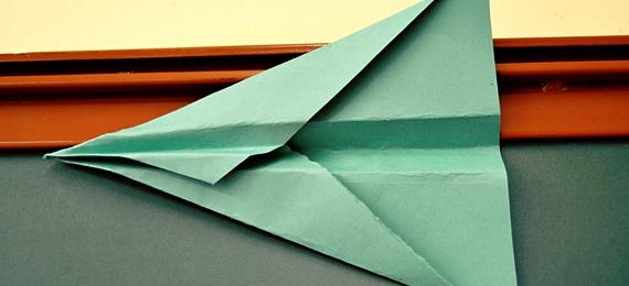 Avión de papel en el borde de una pizarra