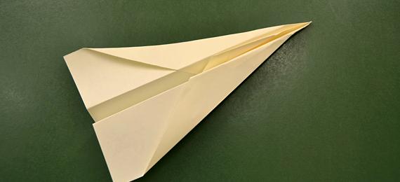Avión de papel sobre una pizarra