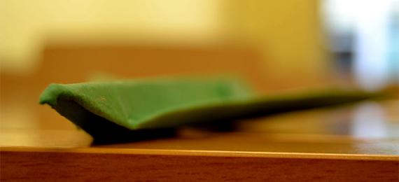 Avión de papel verde sobre una mesa