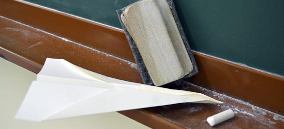 Avión de papel junto a un borrador de pizarra