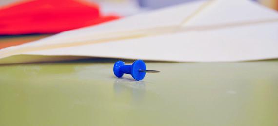Chincheta azul junto a aviones de papel de colores