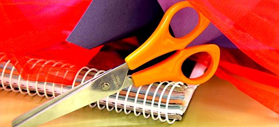 Tijeras junto a cuaderno y papel pinocho de colores