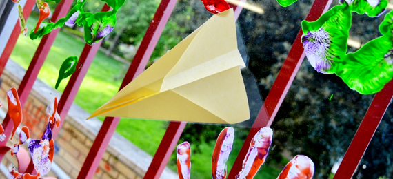 Avión de papel pegado a una ventana decorada con huellas de manos de colores