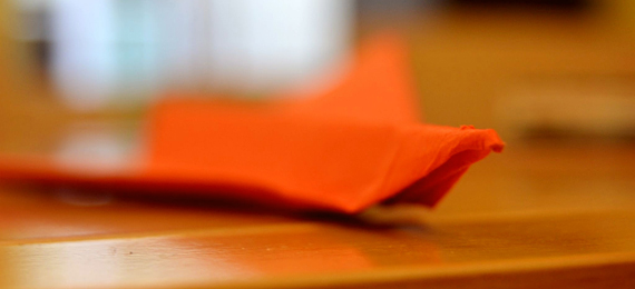 Avión de papel naranja sobre una mesa