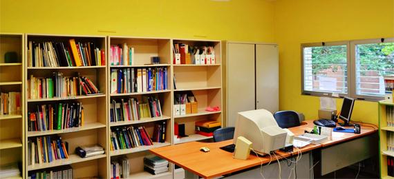 Despacho con estanterías y un equipo informático sobre un escritorio
