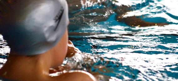 Alumnos y alumnas realizando actividades en una piscina