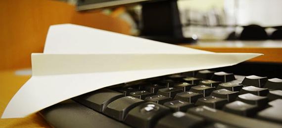 Avión de papel sobre un teclado de ordenador